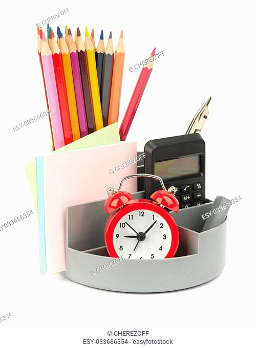 Pencil cup with alarm clock and calculator on isolated white background