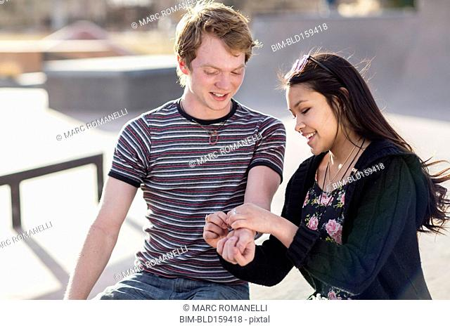 Teenage girl tying bracelet around wrist of boyfriend