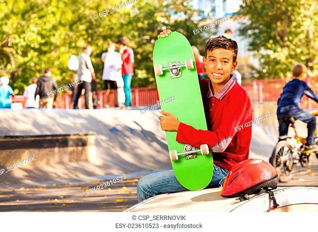 Happy Arabian boy with green skateboard sitting