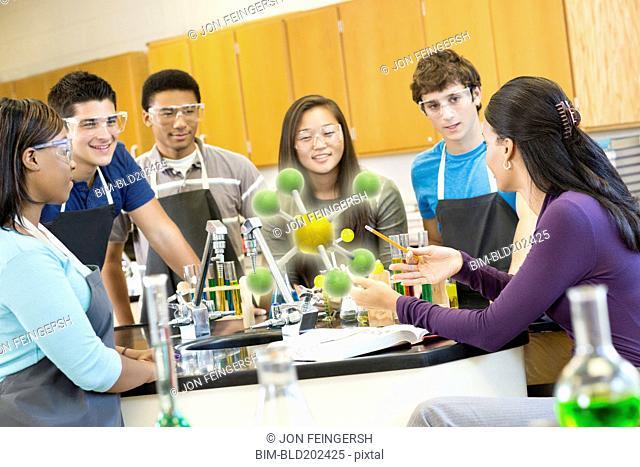 Teacher explaining chemistry model to students