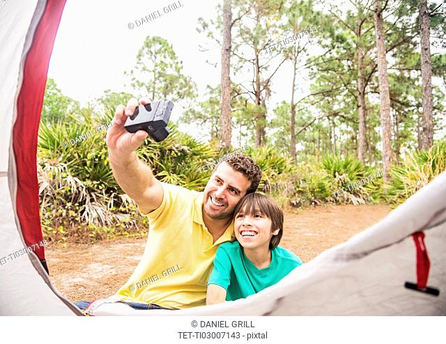 Father and son (12-13) taking selfie in front of tent