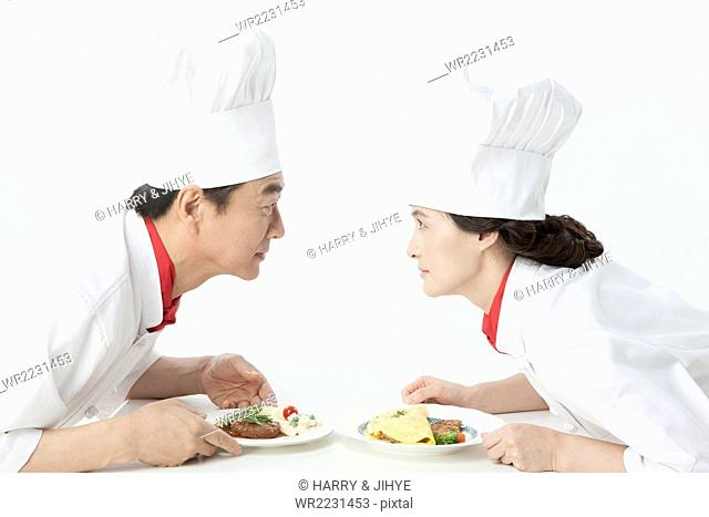 Middle aged male and female cooks staring at each other with a dish each