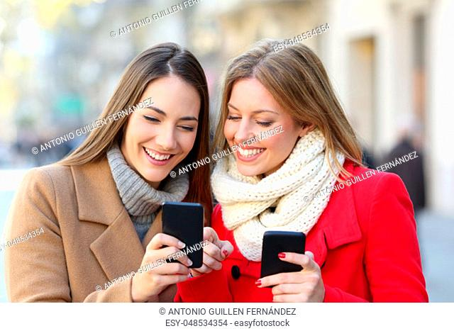 Friends consulting smart phone content in the street in winter