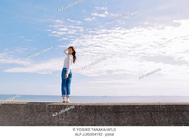 Young Japanese woman standing on concrete wall by the sea