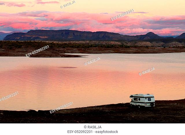 A travel camper is parked on the shoreline of Lake Pleasant, a reservoir near Phoenix, Arizona