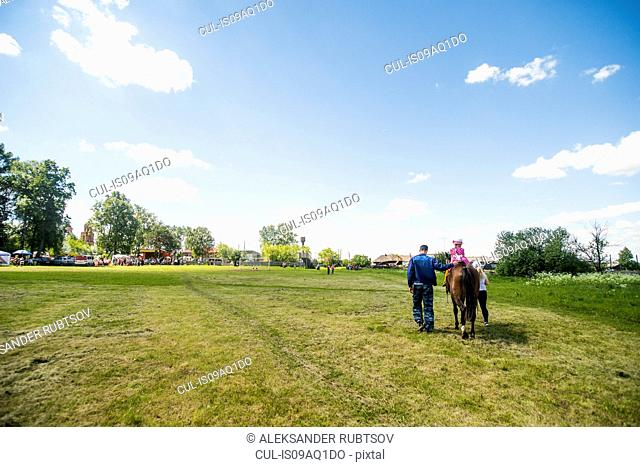Rear view of young man and two girls riding horse in field, Rezh, Sverdlovsk Oblast, Russia