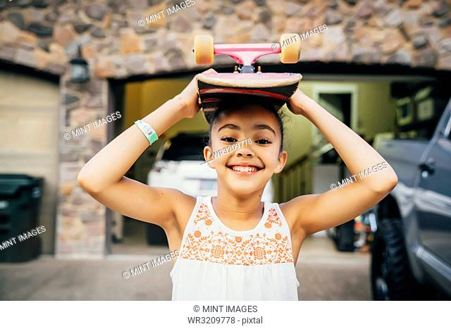 Smiling girl standing in driveway in front of house with skateboard on her head