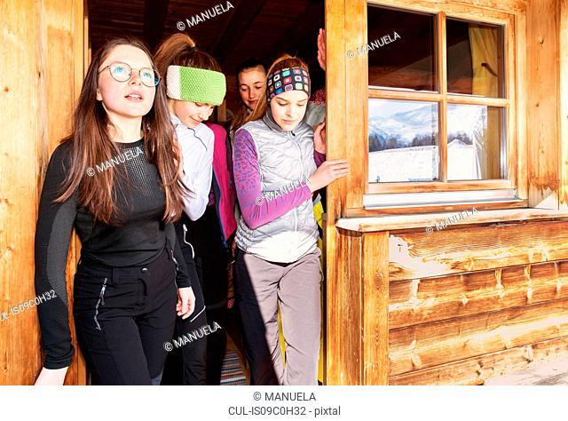 Four teenage girl skiers looking out from cabin doorway, Tyrol, Styria, Austria