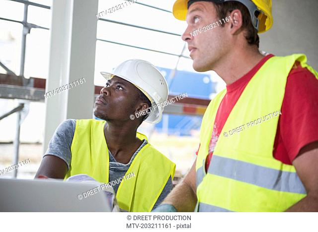Construction workers looking up at building site