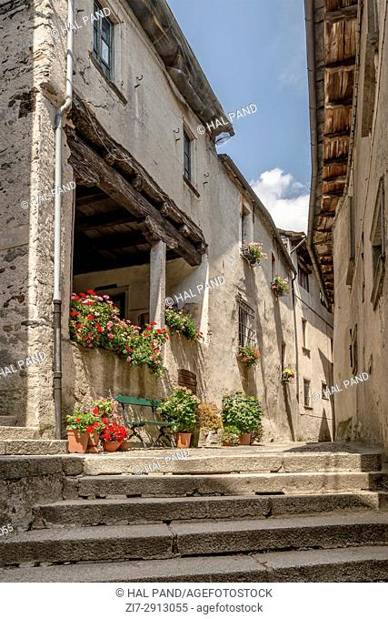 flowers and narrow alley among old buildings on little island at Orta lake, shot on bright summer day on San Giulio island, Novara, Cusio, Italy