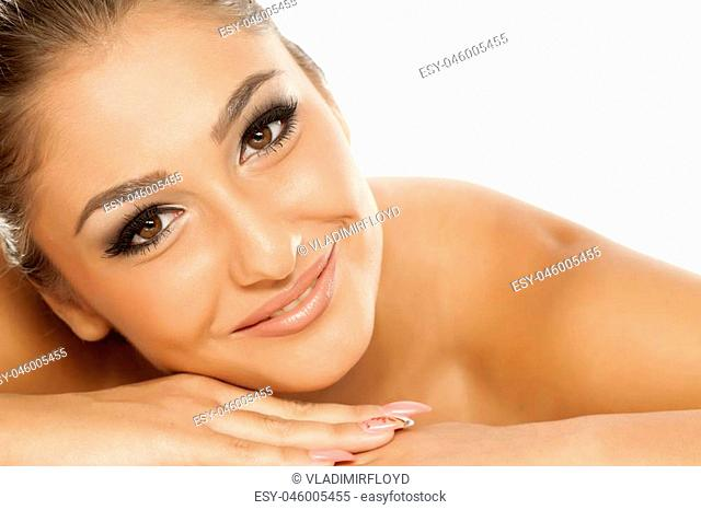 Portrait of beautiful young woman, lying on towel
