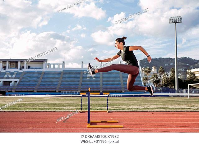 Female hurdler during training on tartan track