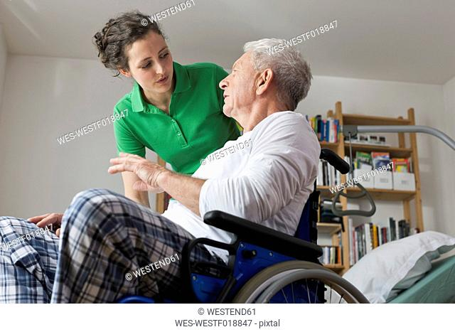 Germany, Leipzig, Man on wheelchair, talking with woman