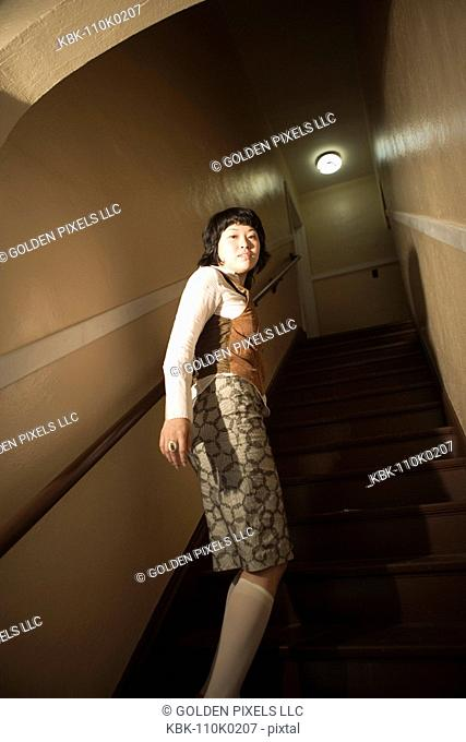 View of a young Asian woman at bottom of staircase