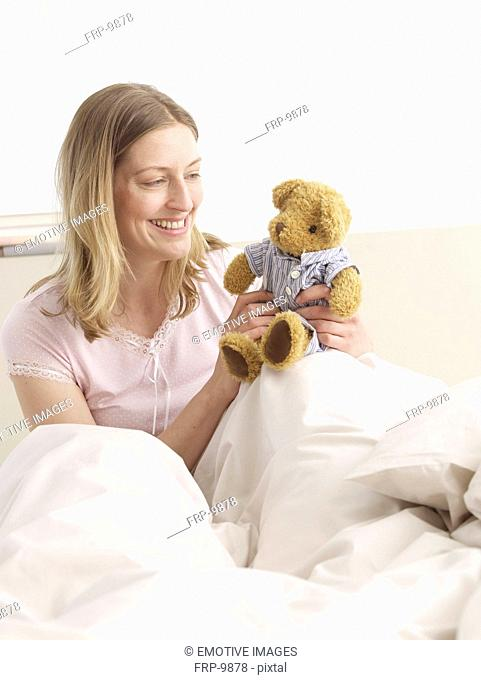 Woman with teddy in bed