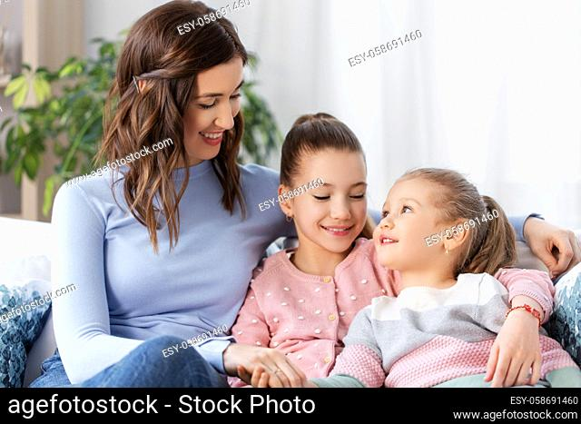 happy smiling mother with two daughters at home