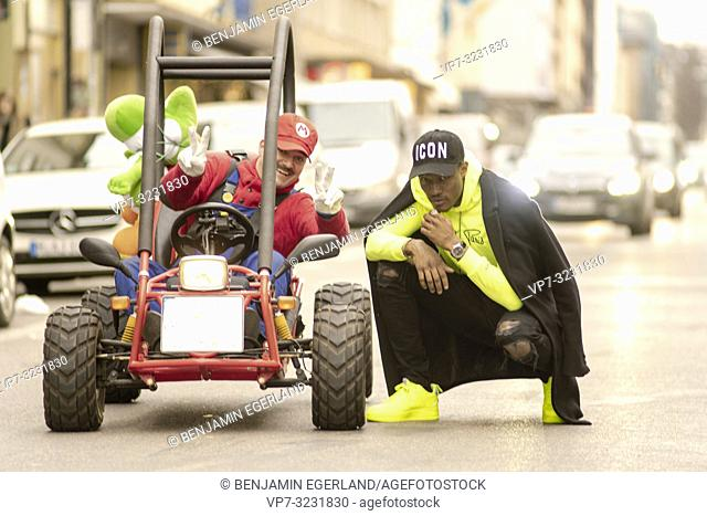 fashionable blogger man posing with Mario Kart driver at city street in Munich, Germany