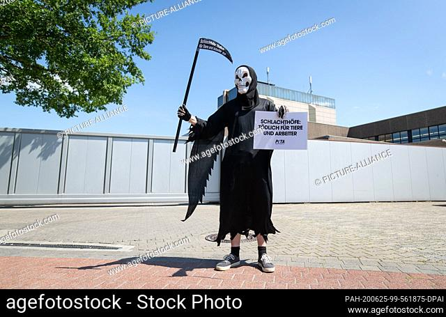 25 June 2020, Lower Saxony, Dissen: An activist of the animal protection organization Peta disguised as death stands in front of a delivery entrance of the meat...