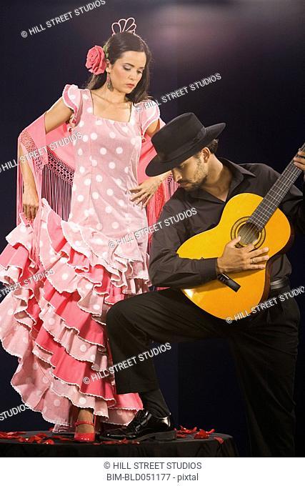 Hispanic female flamenco dancer next to guitar player