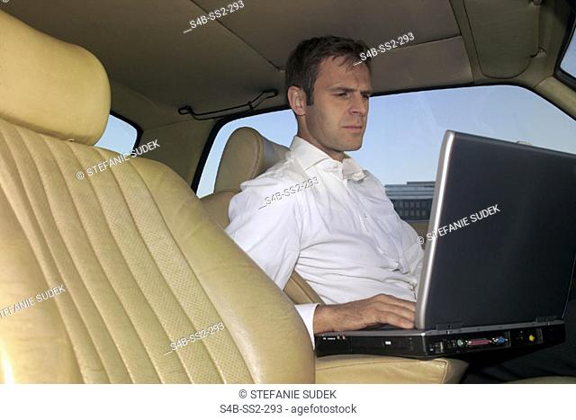 Business man with laptop sitting in a car