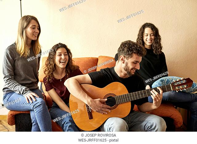 Happy freinds listening to man playing guitar on couch