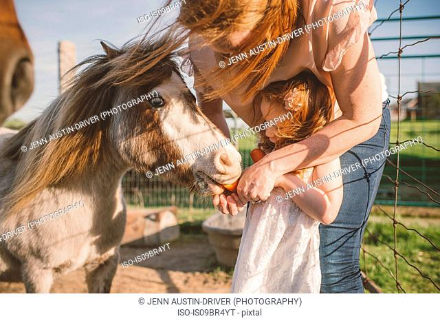 Mother and daughter feeding pony in farm