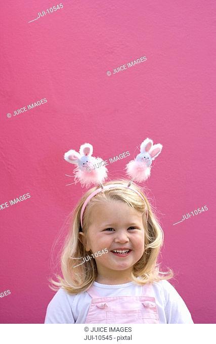 Girl 2-4 wearing bunny rabbit headband by pink wall, smiling, portrait