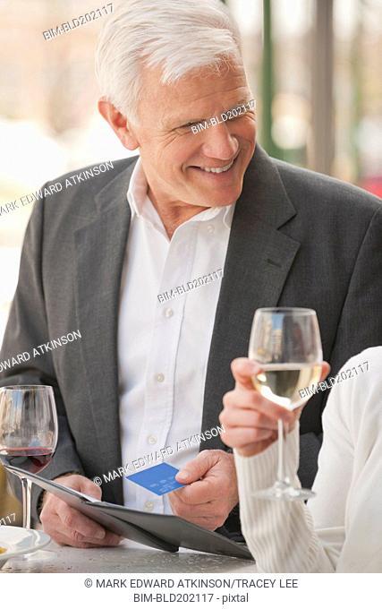 Caucasian couple drinking wine and paying bill