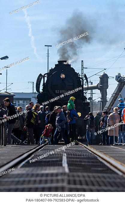 07 April 2018, Germany, Dresden: Several people walk past a steam locomotive of the series 52 during the Dresden steam locomotive meeting