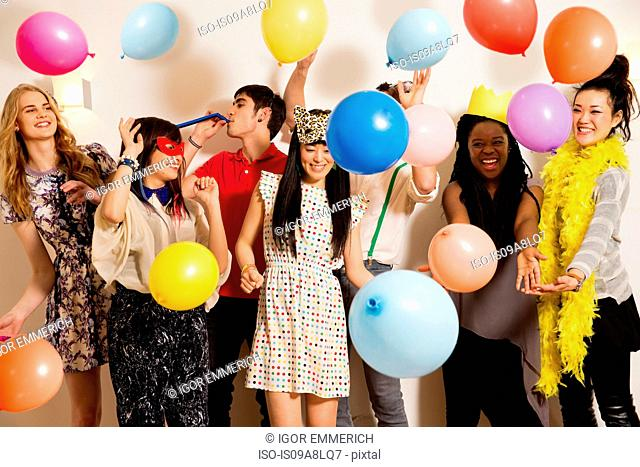 Friends at a party with balloons, studio shot