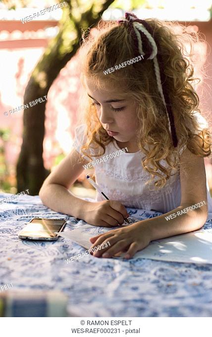 Spain, little girl drawing a picture that she is seeing on a smartphone