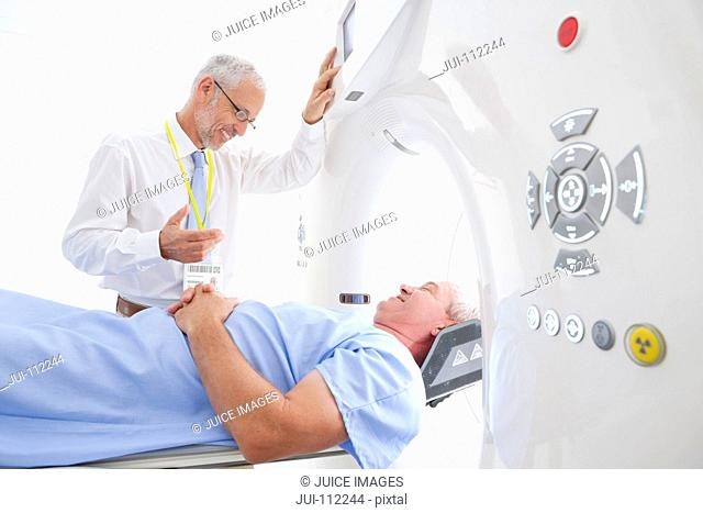Doctor preparing patient for CT scan in hospital