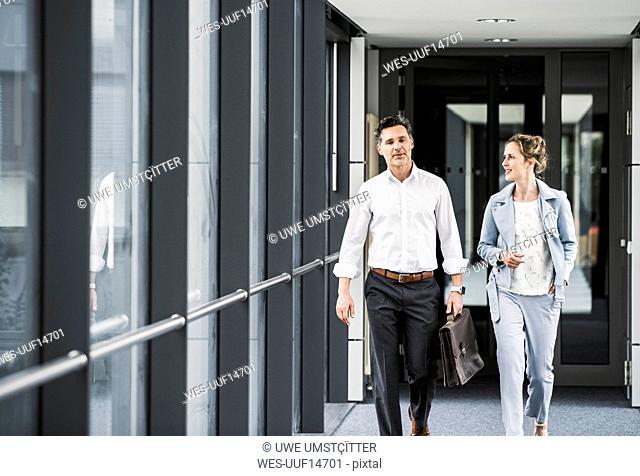 Businesswoman and businessman walking in office passageway