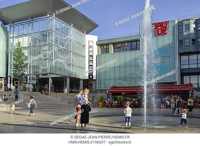 France, Puy de Dome, Clermont Ferrand, Place of Jaude, children with their parents at the foot of a water jet with a shopping mall in the background