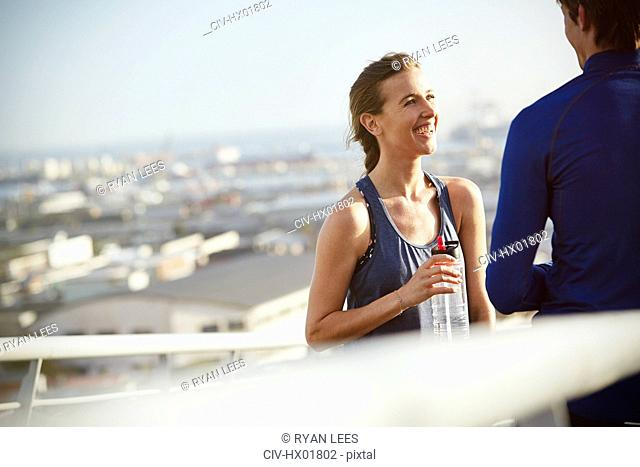 Smiling runner couple resting drinking water on sunny urban footbridge