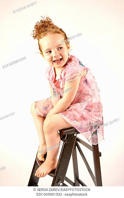 Fashion little girl in rose dress, in catwalk model pose, stock photo