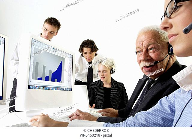 Five business executives working together in an office in front of a computer