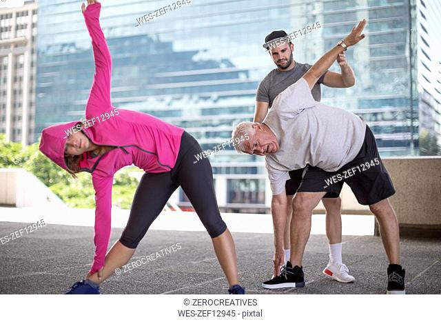 Fitness instructor guiding senior man doing a stretching exercise