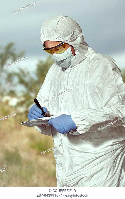 Criminologist technician in DNA free protective suit collecting evidences of probable criminal act