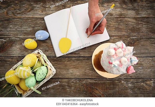 Top view of female hand writing in notebook, straw basket with pained eggs and easter cake with interesting topping are standing on wooden table