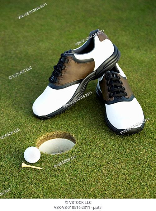 Golf shoes, ball and tee on golf course by hole