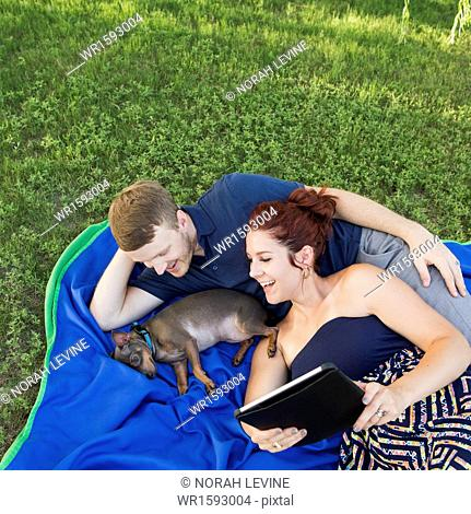 A couple on a blue rug with a small dog. A woman holding a digital tablet