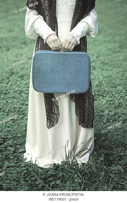 a woman with a brown shawl and a blue suitcase