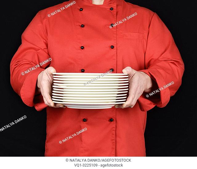 cook in red uniform holds in his hands a stack of round white empty plates