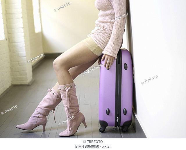 Woman in mini skirt sitting on suitcase