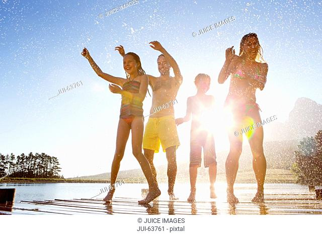 Happy family having water fight on jetty