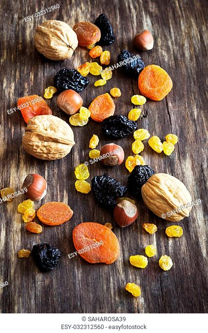 various dried fruits and nuts on an old wooden background. health and diet food