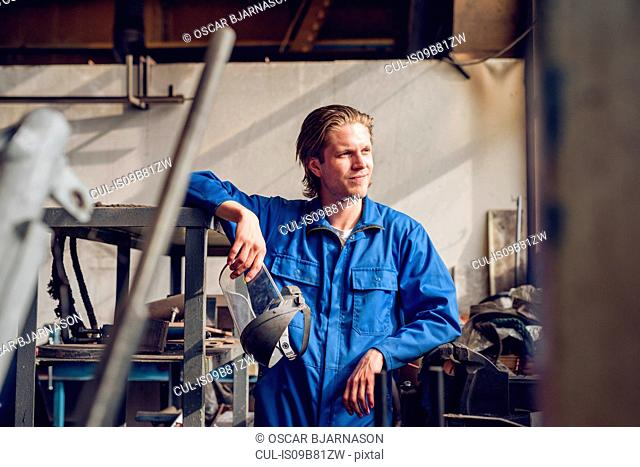 Portrait of factory worker, wearing protective clothing, in manufacturing plant