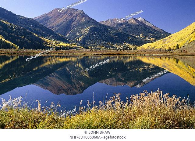RED MOUNTAIN reflected in Crystal Lake with Quaking Aspens in autumn colours Populus tremuloides San Juan Mountains, Colorado, USA