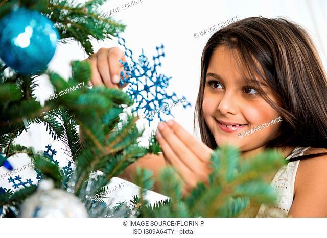 Smiling girl decorating Christmas tree